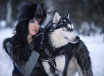 Young attractive woman with husky dog looking aside in snowing park